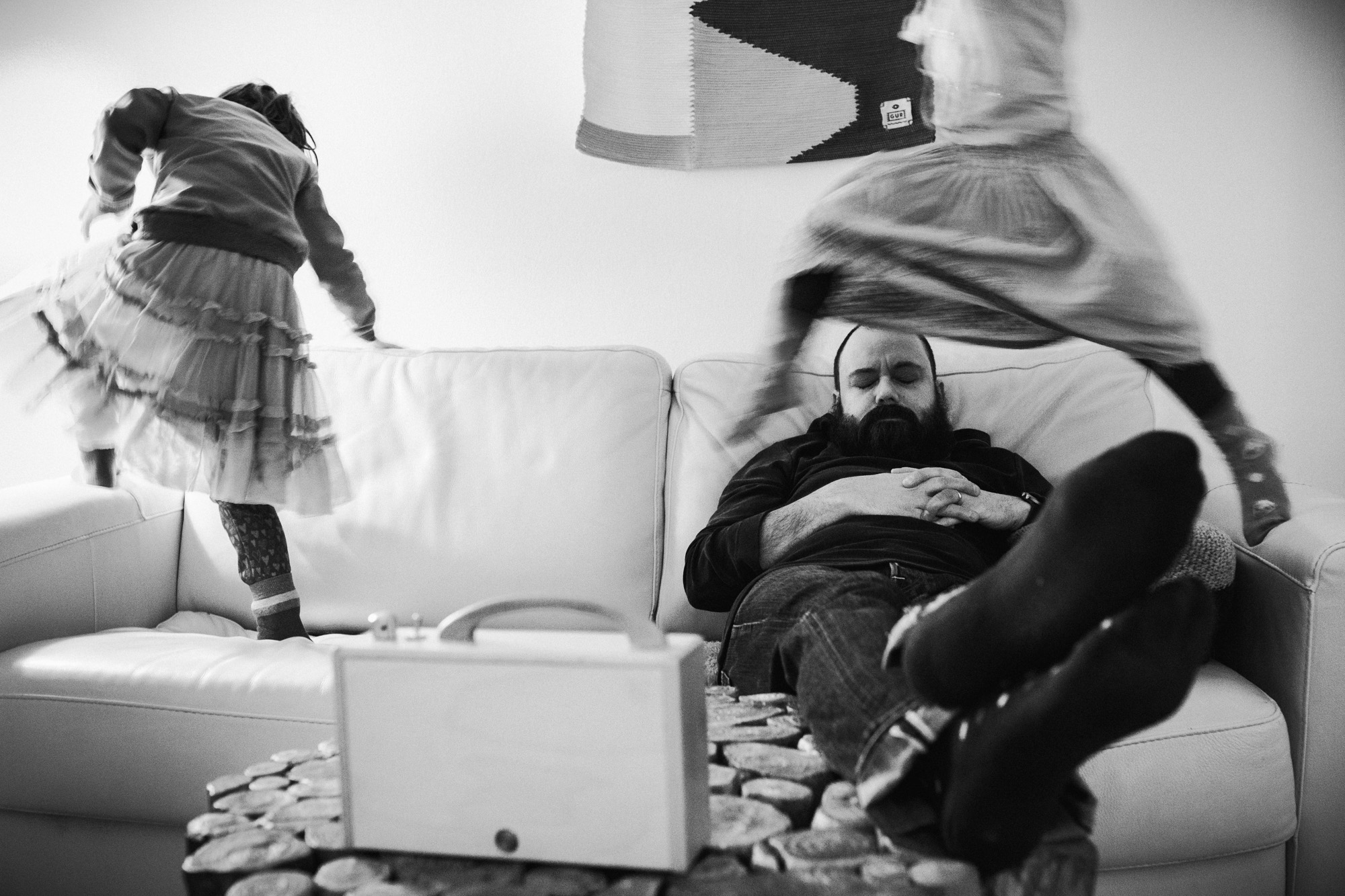 Ein Vater schläft auf der Couch. Kinder springen schnell um ihn herum.