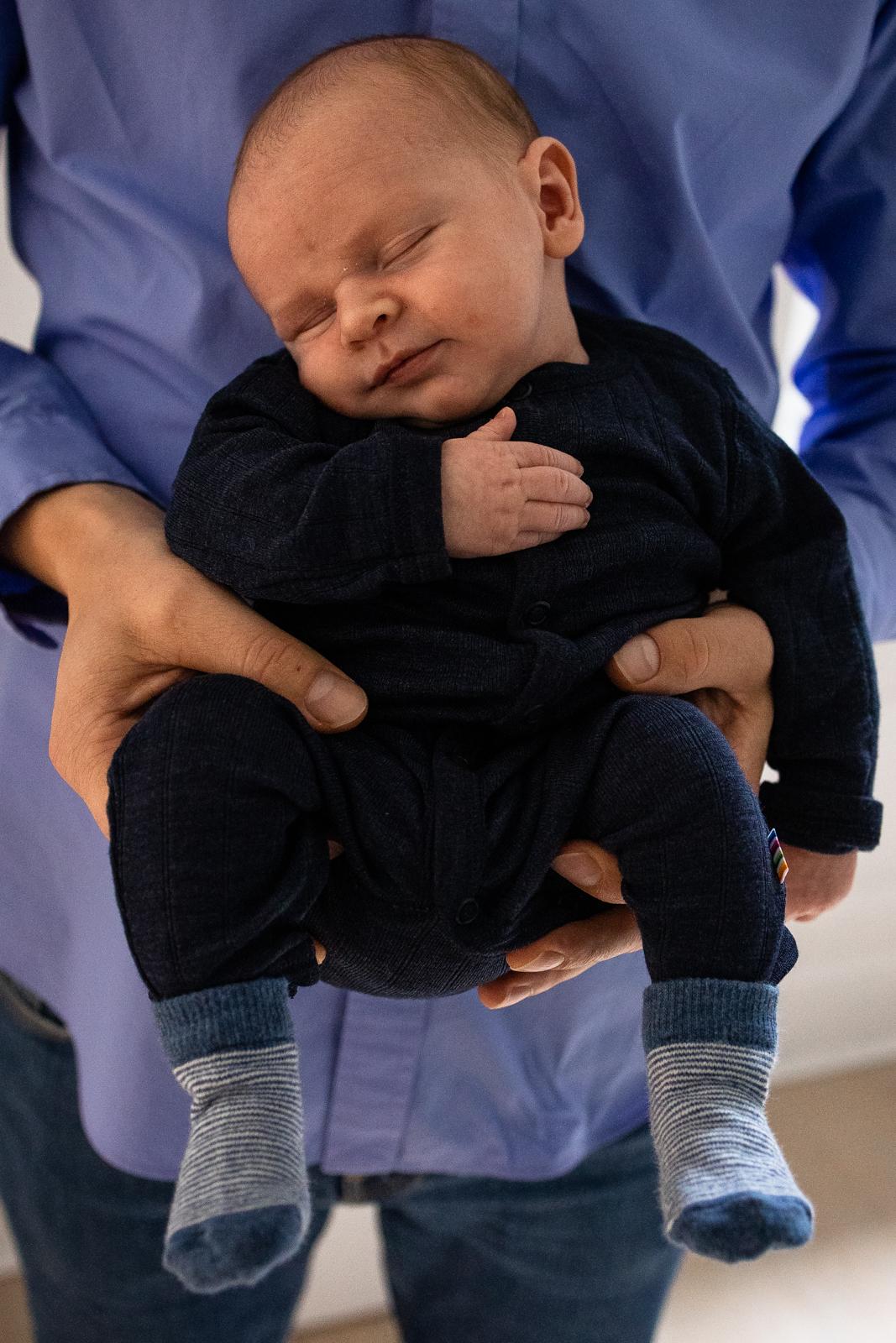 Ein Baby schläft in den Armen seines Vaters.