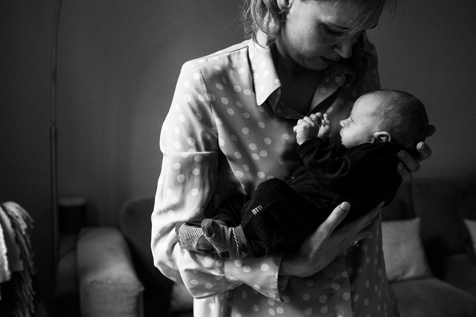 Mutter hält vorsichtig ihr Neugeborenes.