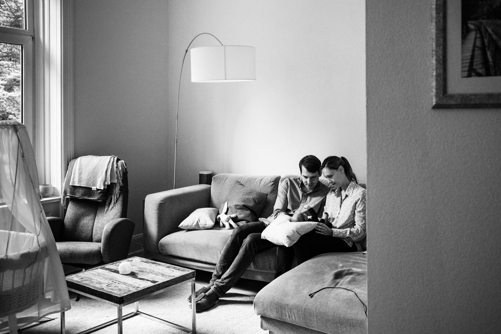 Ein Paar mit Baby im Wohnzimmer.
