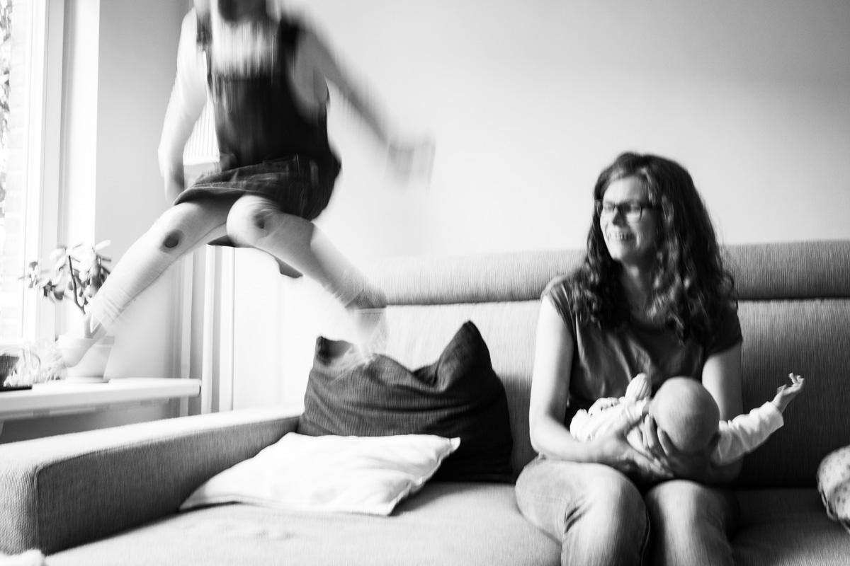 Foto in Bewegung. Man sieht eine Mutter, die auf der Couch sitzt und ihr Baby auf dem Schoß hält. Die große Schwester springt auf der Couch. Mutter schaut mit einem Lächeln zu ihrer Tochter.