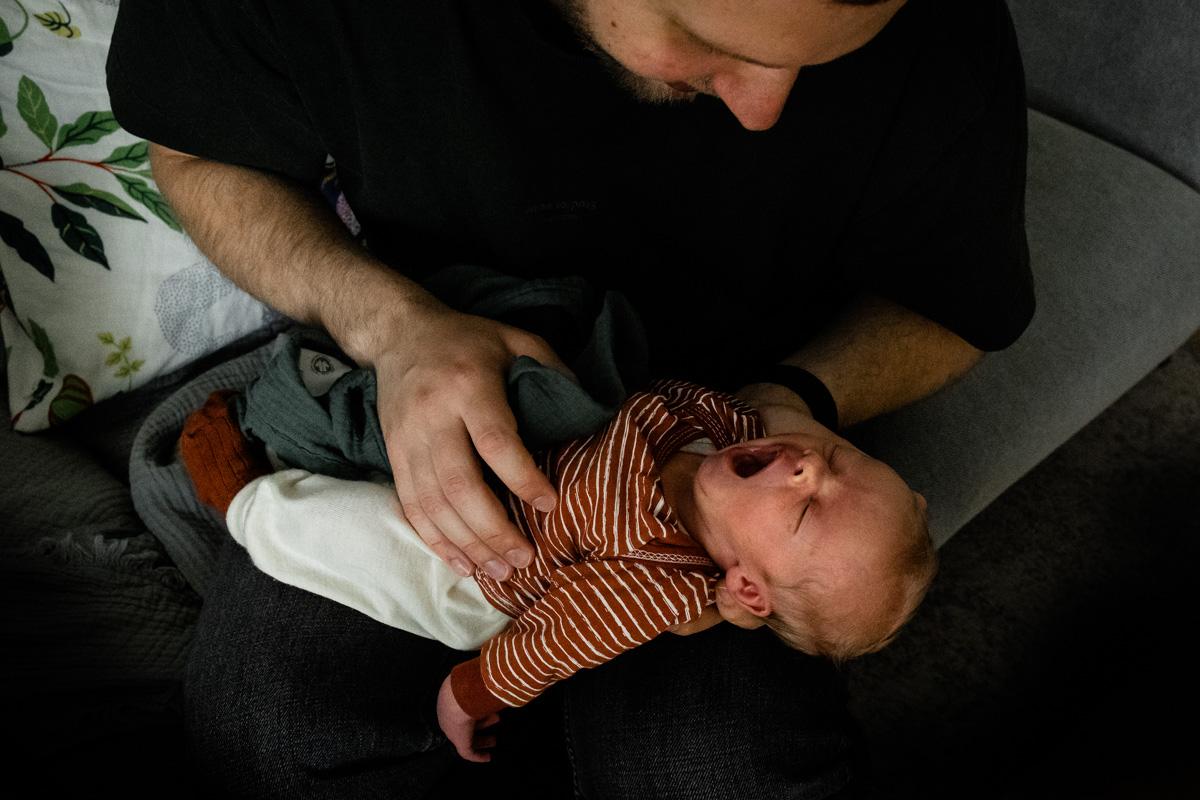 Vater hält ein gähnendes Baby auf dem Arm.