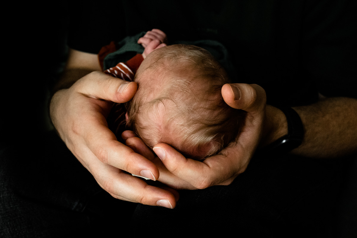 Babyhaare, Erwachsenenhände halten den Kopf eines Babys.